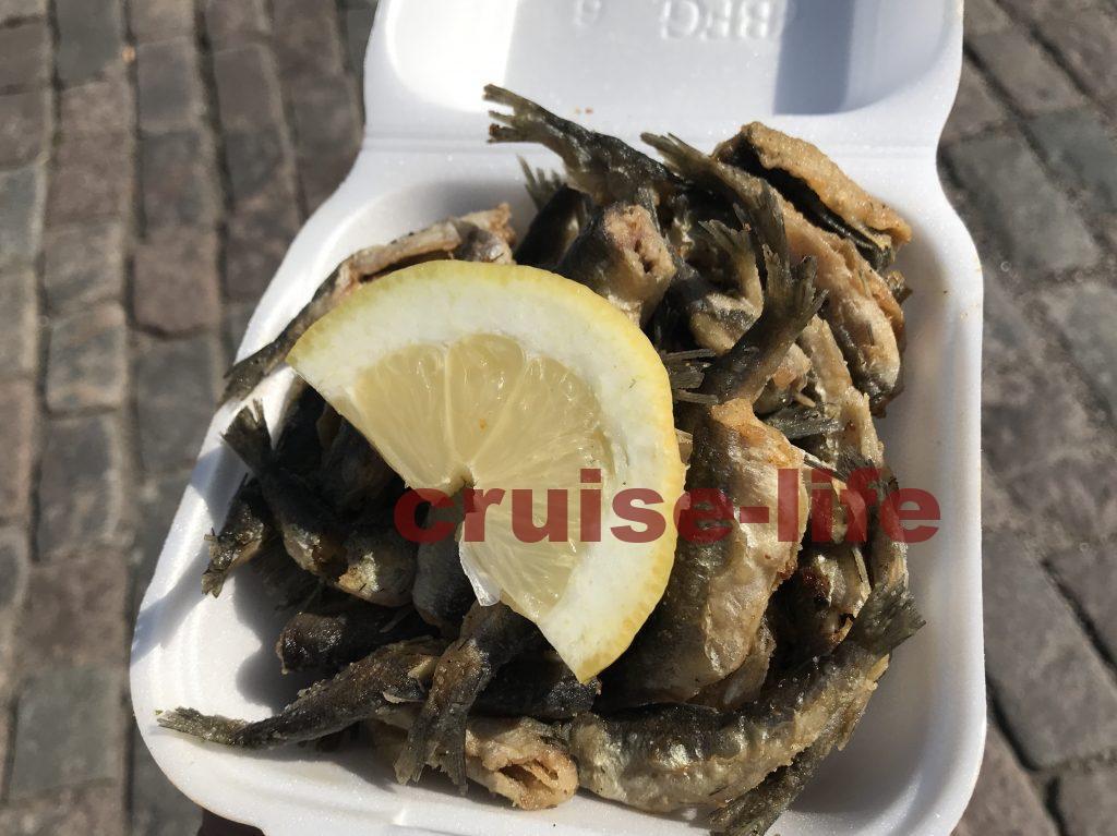 ヘルシンキの屋台のマーケットで小魚料理を買う
